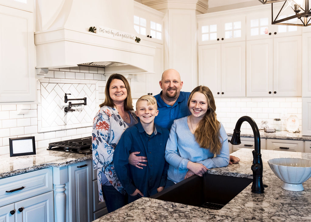 A family standing in a kitchen.